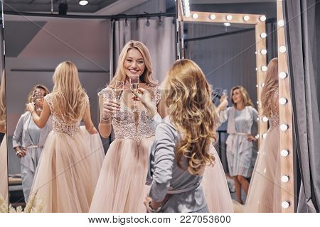 To Us! Attractive Young Women Toasting Each Other And Smiling While Standing In The Fitting Room