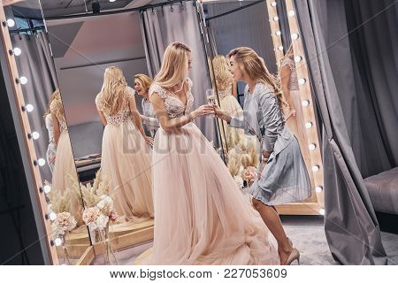 So Happy! Attractive Young Women Toasting Each Other And Smiling While Standing In The Fitting Room