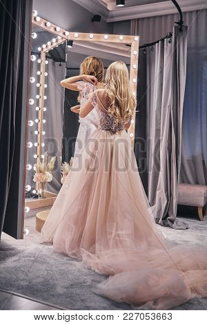 Fits Perfect. Full Length Rear View Of Young Woman Adjusting A Dress On Her Girlfriend While Standin