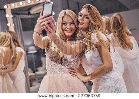 Capturing The Moment. Young Beautiful Women In Amazing Wedding Dresses Smiling While Taking Selfie I