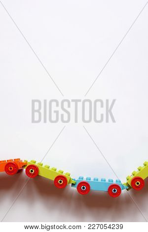Colorful Toy Cars Connected Each Others. Educational Toys. Plastic Bricks Toys. Four Toy Cars On Whi