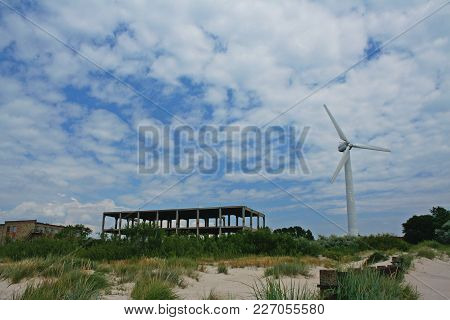 Bright Picture Of Wind Turbine Standing Near Unfinished Building.
