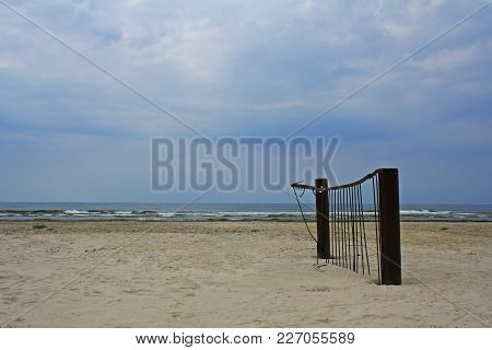 A Piece Of Rusty Destructed Fence Abandoned In The Sand On A Seaside.