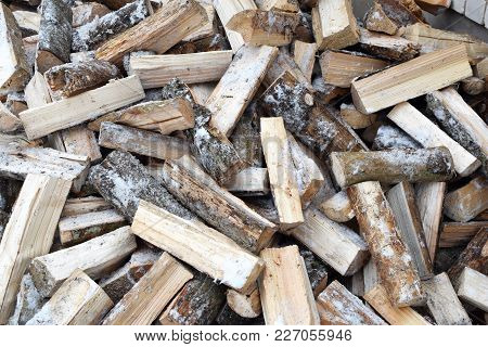 Firewood Background - Chopped Firewood On A Stack. Chopped Snowy Firewood Logs In A Pile.