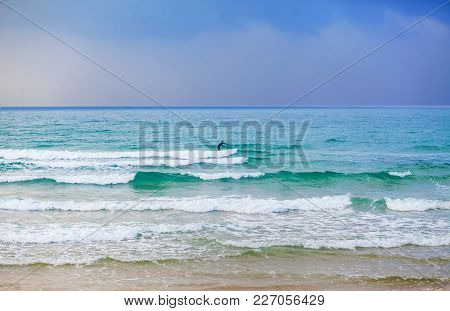 Lonely Surfer Paddling The Waves On His Board