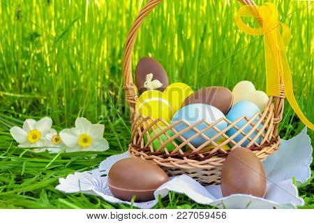 Easter Basket With Easter Chocolate Eggs And Colored Eggs On Green Grass Background.