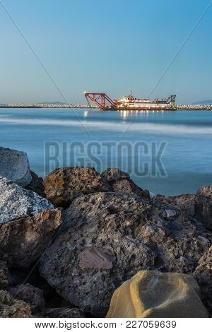 Dredge Boat Guided By The Morning Lights Working In The Harbor With Boulders In The Foreground.