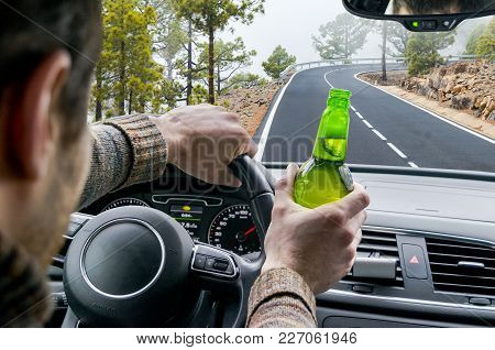 Drunk Young Man Driving A Car On The Road With A Bottle Of Beer. Don't Drink And Drive. Drunk Drivin
