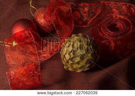 Golden And Red Christmas Toys With Red Tape On The Dark Cloth Background