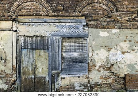 Old Wall From Red Brick With The Closed Wooden Door And Window