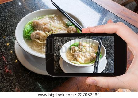 Travel Concept - Tourist Photographs Local Chinese Soup Dim Sum With Noodle In Cafe In Yangshuo Coun