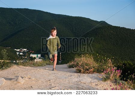 Six Year Old Boy Running On A Mountain Road At Sunset With Town View. Cool Summer Evening In The Mou