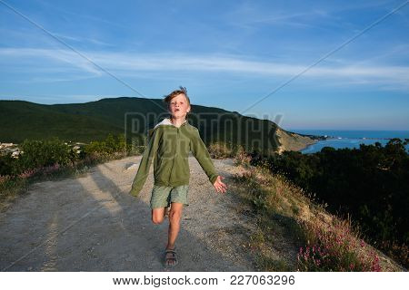 Six Year Old Boy Running On A Mountain Road At Sunset With Town And Sea View. Cool Summer Evening. F