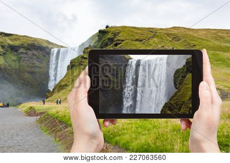 Travel Concept - Tourist Photographs Water Flow Of Skogafoss Waterfall In Katla Geopark On Icelandic