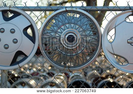 Many Hubcaps Tied To A Chain Linked Fence