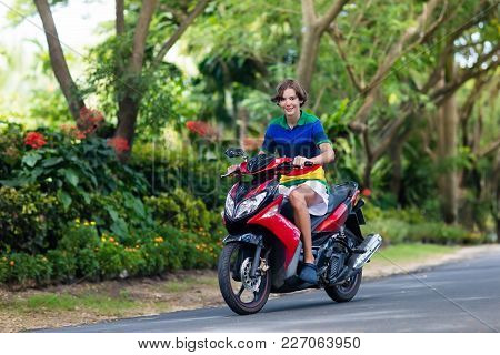 Teenager And His Little Brother Riding Quad Bike On Tropical Beach. Active Teen Age Boy On Quadricyc