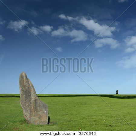 Ancient Standing Stones With Couple Walking On Horizon
