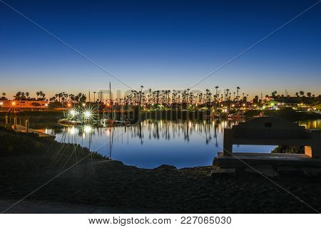 Clear Reflection Of Palm Trees, Boat Masts, And Lights In The Calm Ocean Water Of Ventura Marina At