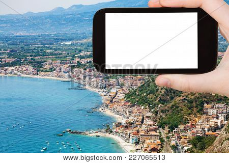 Travel Concept - Tourist Photographs Ionian Sea Shore With Giardini Naxos Town In Sicily Italy In Su