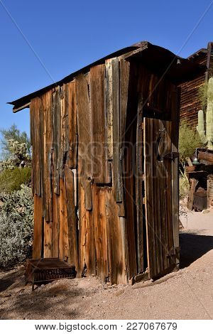 Side Profile Of An Old Cedar Outdoor Outhouse With A Cacti Tree In The Background