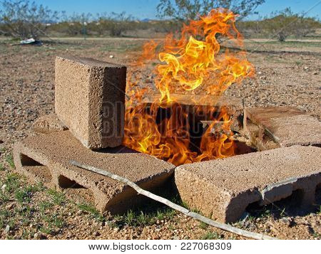 The Flames Of A Burning Fire In A Pit Lined With Cinder Blocks.