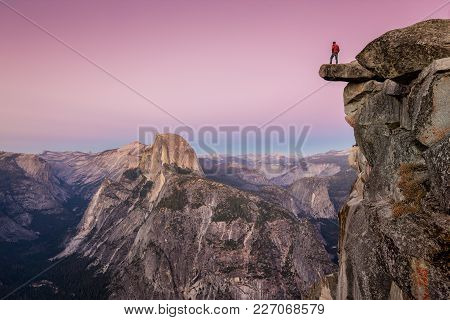 A Fearless Male Hiker Is Standing On An Overhanging Rock At Glacier Point Enjoying The Breathtaking