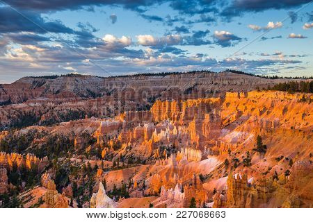 Classic View Of Bryce Canyon National Park In Beautiful Golden Morning Light At Sunrise With Blue Sk
