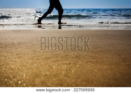 A Silhouette Of Man Running On A Beach Unfocused