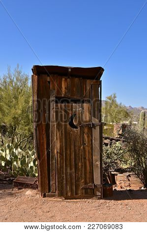 An Old Cedar Outdoor Outhouse With A Cactus Trees In The Background.