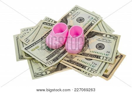 Horizontal Shot Of A Pair Of Pink Plastic Baby Booties Sitting On Top Of A Pile Of Twenty And Ten Do