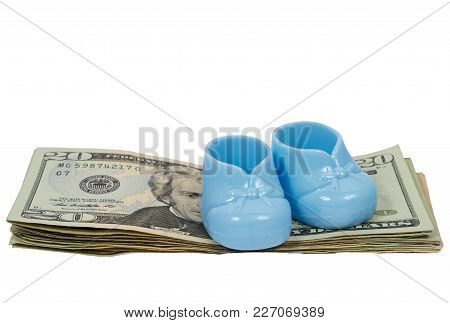 Horizontal Shot Of A Pair Of Blue Plastic Baby Booties Sitting On A Stack Of Twenty Dollar Bills On