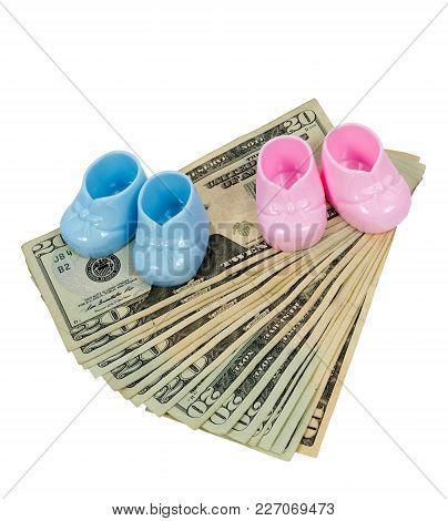 Vertical Shot Of A Pair Of Pink And Blue Plastic Booties Sitting On Fanned Out Twenty Dollar Bills W