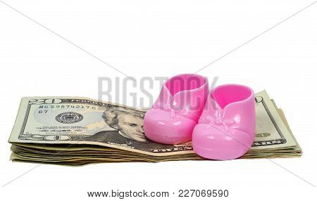 Horizontal Shot Of A Pair Of Pink Plastic Baby Booties Sitting On Top Of A Pile Of Twenty Dollar Bil