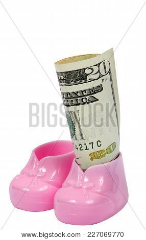 Vertical Shot Of A Pair Of Pink Plastic Baby Booties With A Rolled Twenty Dollar Bill In One.  The O