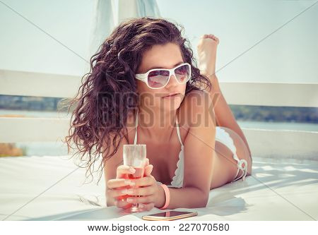 Woman Drinking Champagne At The Beach