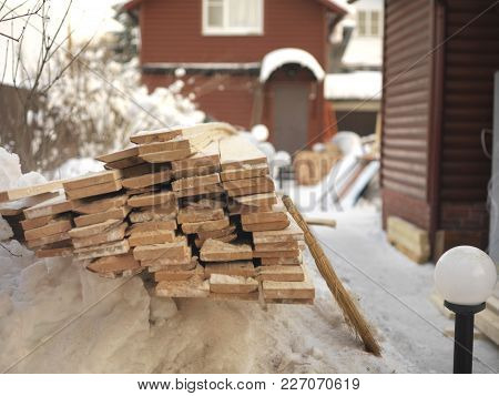 Stack Of Planks On The Snow In The Foreground, A House Under Renovation In The Background
