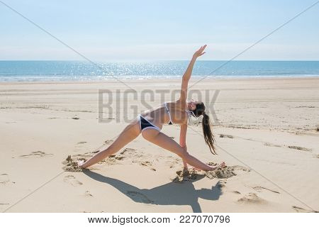 Unrecognized Woman In Bikini Doing Yoga Stands In A Triangle Position On The Beach