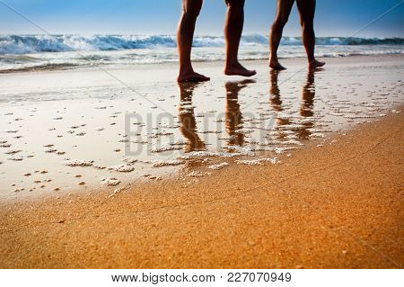 Photo Of Legs Of Two People Walking On The Beach In The Sunset Unfocused
