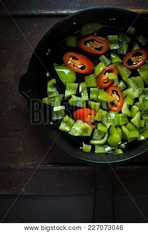 Green Pepper And Chili On A Cast-iron Frying Pan Vertical