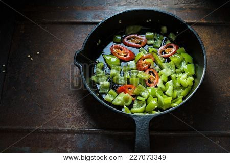 Green Pepper And Chili On A Cast-iron Frying Pan Side View Horizontal