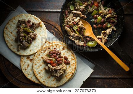 Tortilla With Filling On Parchment And Frying Pan On Table Horizontal