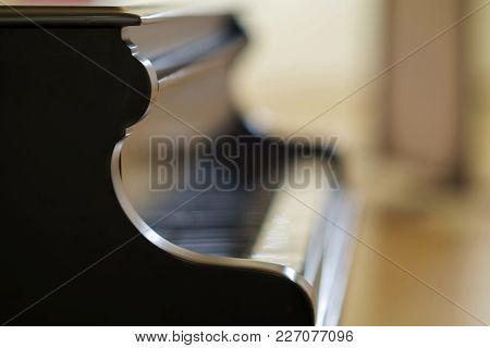 Black Grand Piano With Blurry Brown Background