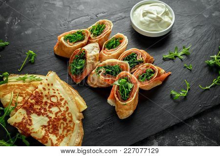 Crepes Pancakes Rolls With Smoked Salmon Stuffed With Wild Rocket Salad Filling Served On Stone Boar