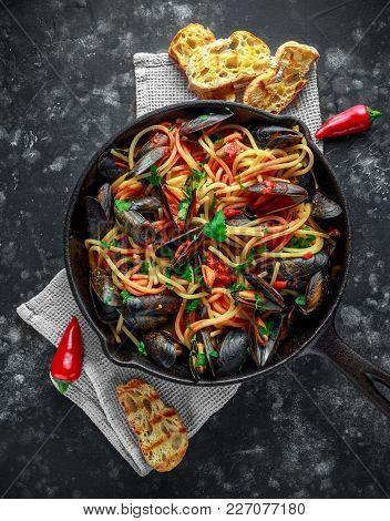 Homemade Pasta Spaghetti With Mussels, Tomato Sauce, Chilli And Parsley In Rustic Skillet, Pan. Sea