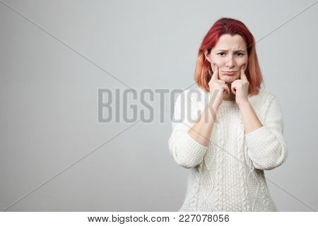 Portrait Of Gloomy Redhead Girl Stretching Mouth With Fingers, Making Fake Smile While Feeling Sad,