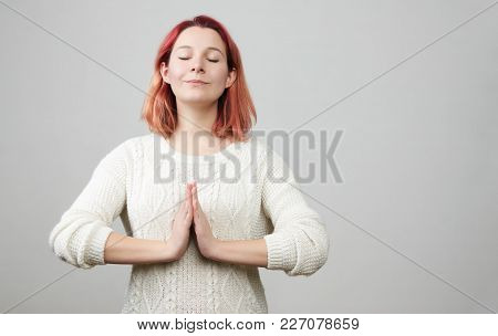 Portrait Of Cute Redhead Caucasian Female Model Standing With Hands In Pray Position In White Sweate