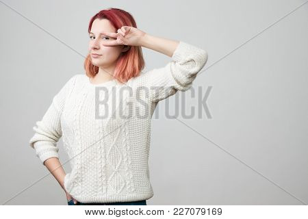 Happy Redhead Female Model Showing Victory Sign Near Eye And Looking Through It, Smiling Cheerfully
