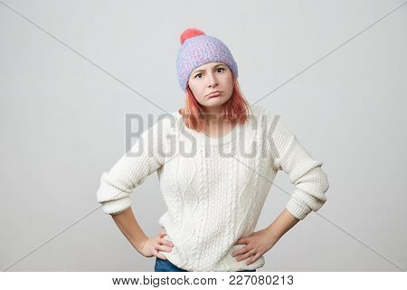 Portrait Of A Young Beautiful Red-haired Girl In Knitted Hat And Sweater Indignantly And Strictly Lo