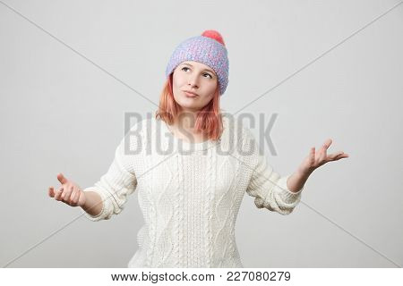Young Woman In Knitted Hat And Sweater Gesturing Skeptical Expressing Disagreement With Facial Expre