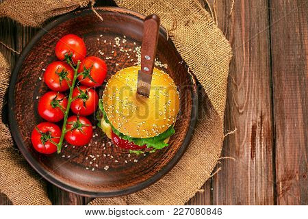 Appetizing Rustic Burger With Bunch Of Tomatoes On Wooden Table.